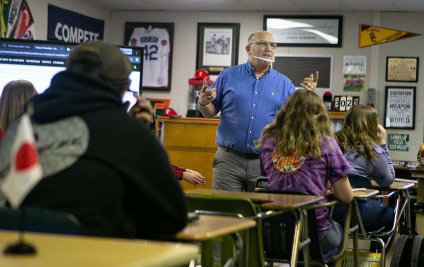 Teacher Bob Anderson speaks at the front of his classroom to students sitting at desks.