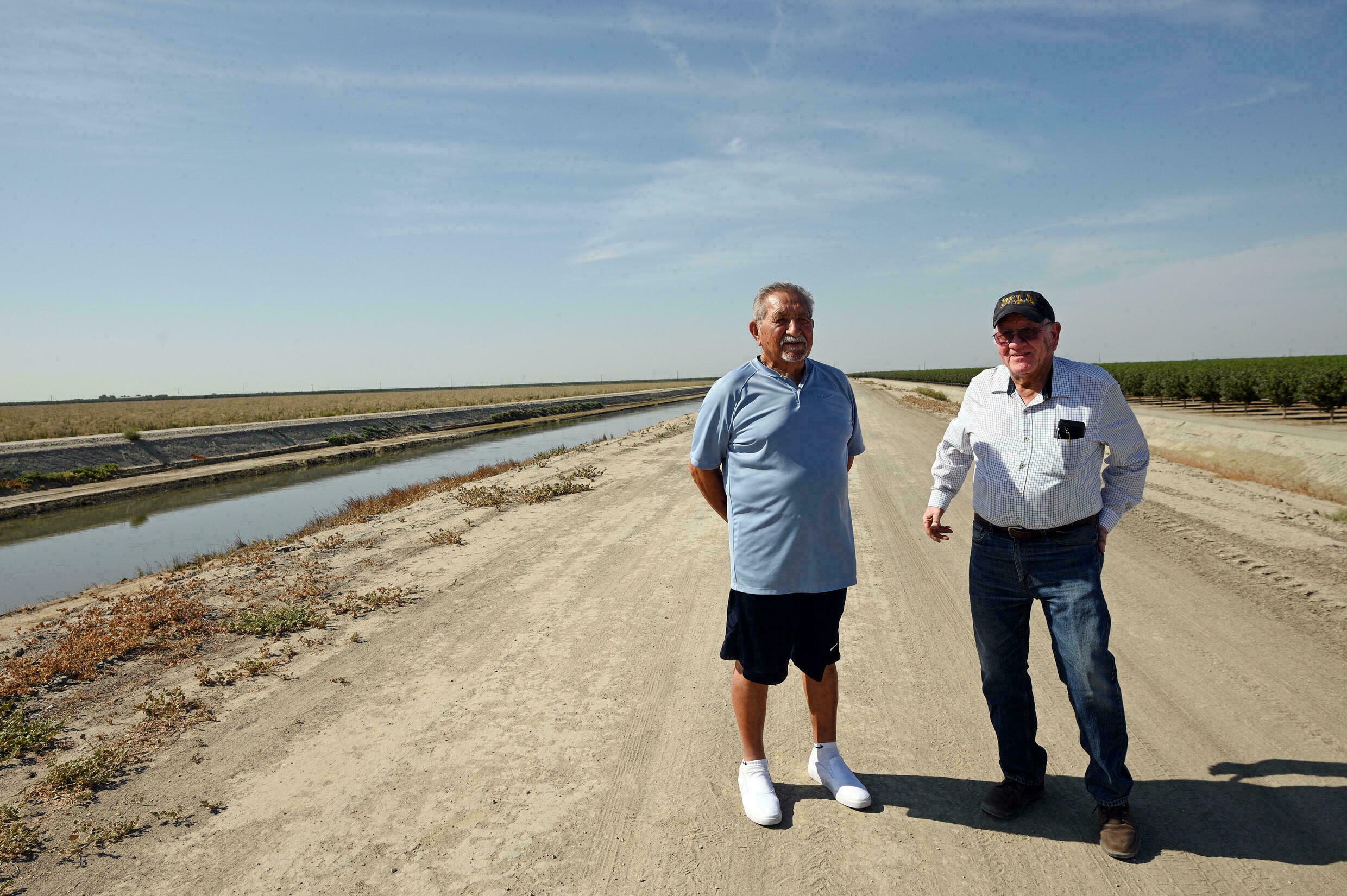 Raul Gomez (L) and Greg Ojeda, standing on July 23, 2021 near a levee in Corocoran, California which was raised in 2017 for fear of floods -- that have yet to come