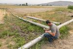 Justin Grant opens an irrigation pipe that allows water from his agriculture well to move into nearby cattle grazing fields, Saturday, July 24, 2021, in Klamath Falls, Ore. Dozens of domestic wells have gone dry in an area near the Oregon-California border where the American West's worsening drought has taken a particularly dramatic toll.