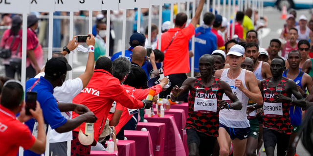 Competitors run past the water station during the men's marathon at the 2020 Summer Olympics, Sunday, Aug. 8, 2021, in Sapporo, Japan.